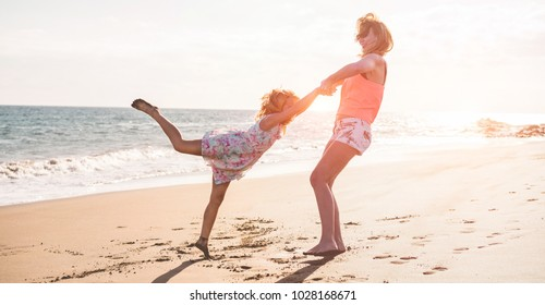 Mother and daughter having fun on tropical beach with sun light in background - Mum playing with her kid in holiday vacation next to the ocean in sunny day - Family lifestyle, travel and love concept