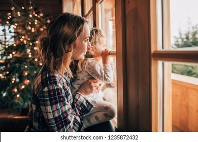 Mutter und Tochter haben Spaß am Weihnachtsmorgen. Kostbarer Familienmoment, junge Mutter spielt mit ihrer kleinen Tochter am Fenster, Winterlandschaft.