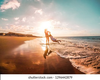 Mother and daughter having fun on tropical beach - Mum playing with her kid in holiday vacation next to the ocean - Family lifestyle and love concept - Focus on silhouettes