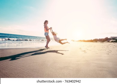 Mother and daughter having fun on tropical beach - Mum playing with her kid in holiday vacation next to the ocean - Family lifestyle and love concept - Sun color tones filter - Focus on silhouettes