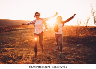 Mother and daughter having fun outdoor during sunset and running