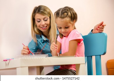 Mother and daughter having fun painting together
