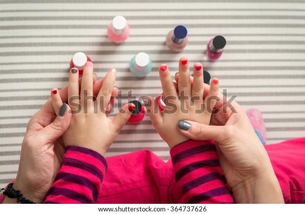 Moeder en dochter hebben plezier schilderen vingernagels, familie tijd concept, uitzicht van boven