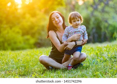 Mother and daughter having fun in the park. Happy family concept. Beauty nature scene with family outdoor lifestyle. Happy family resting together. Happiness and harmony in family life.