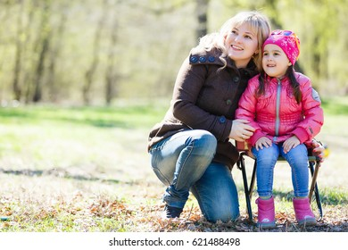 Mother and daughter having fun in the park.  Beauty nature scene with family outdoor lifestyle. Happy family resting together. Happiness and harmony in family life. Mom and little daughter outdoors