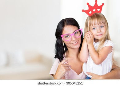 Mother and daughter having fun with photo props