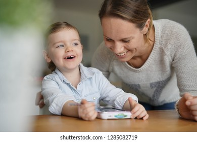 Mother and daughter having fun playing with child's tablet at home