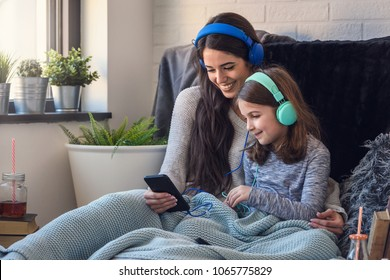 Mother and daughter having fun with smart phone and headphones. Family quality time