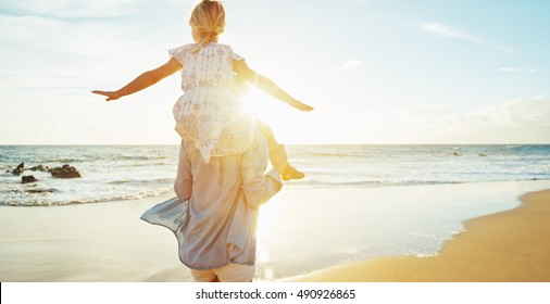 Mother and daughter having fun walking and playing on the beach at sunset