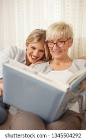 Mother and daughter having a great time while looking through old family photo album. Happy family moments at home