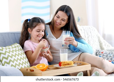 Mother and daughter having healthy breakfast on sofa in room