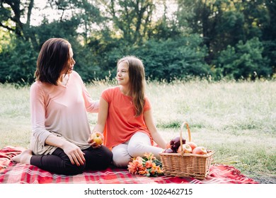 Mother and daughter having a picnic together and talking