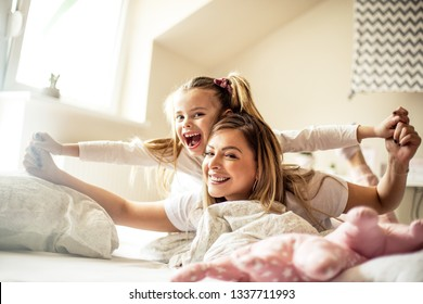 Mother and daughter having piggyback ride in bed. Portrait.