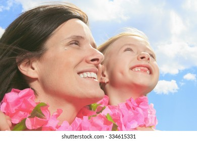 A mother with is daughter having a pink necklace