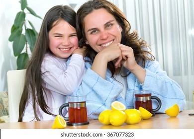 Mother and daughter having tea, eating lemon, honey to heal