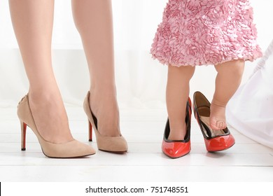 Mother and daughter in high heeled shoes standing on floor