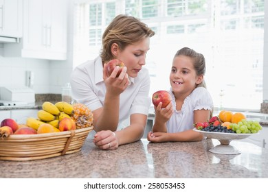 Mother and daughter holding apples at home in kitchen