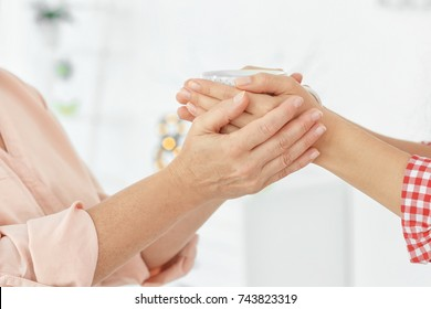 Mother and daughter holding cup in hands indoors, closeup