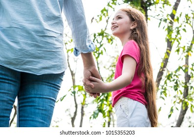 Mother and daughter holding hand together while walking in the park. Family and lifestyle concept