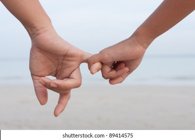 Mother and daughter holding hand together on the beach