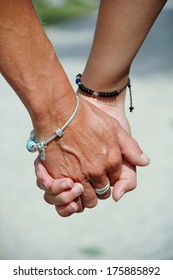Mother and daughter holding hands.