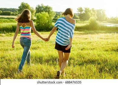 Mother and daughter holding hands, back view. Photo on nature in a sunny summer day.