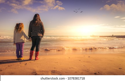 A mother and a daughter holding hands, looking the sunset whith dream effect