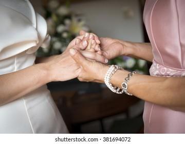 Mutter und Tochter, die am Tag ihrer Hochzeit Händchen halten