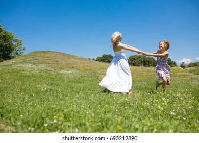 Mother and daughter holding hands, spinning, smiling. Happy woman with her child having fun in a meadow.