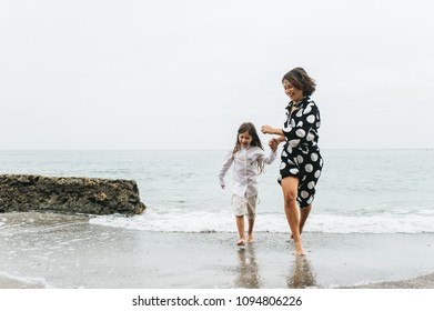 Mother and daughter holding hands and walking on beach. Mom and dauther happy family lifestyle concept