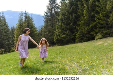 mother and daughter holding hands and walking on meadow at forest