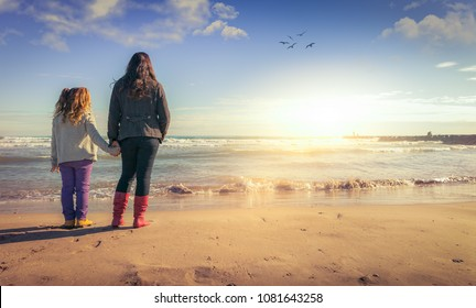 A mother and daughter holding hands, watching the sunset