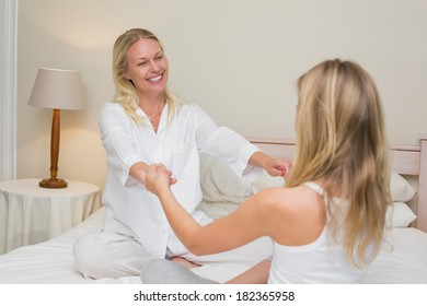 Mother and daughter holding hands while sitting in bed at home