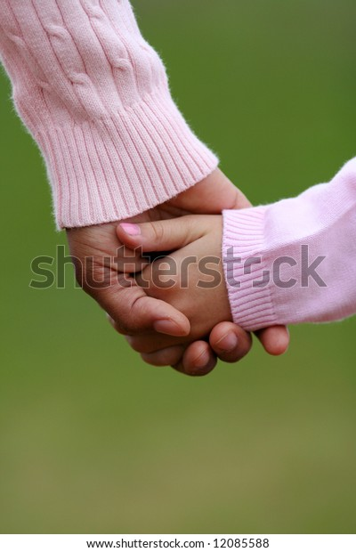 Mother and daughter holding hands while walking together