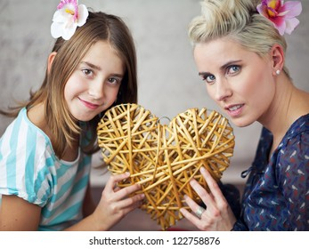 Mother and daughter holding a heart