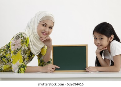mother and daughter holding small blackboard