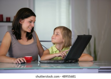 Mother and daughter at home with laptop