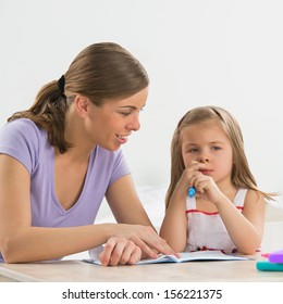 Mother and daughter at home. Mom teaches little girl to draw and write