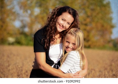 mother and daughter hugging in country field with texture overlay