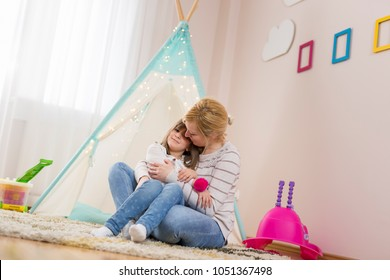 Mother and daughter hugging and kissing, smiling having fun together; daughter sitting in her mother's lap