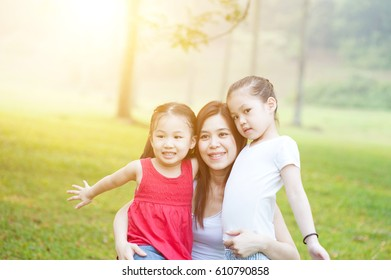Mother and daughter hugging in love playing in the park. Family outdoor fun, morning with sun flare.