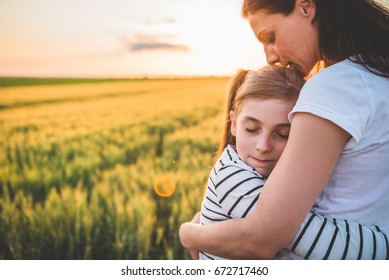 Mother and daughter hugging at wheat field during sunset