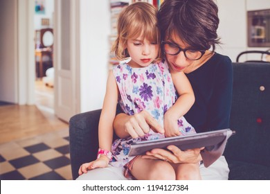 mother and daughter indoor using tablet – learning, entertainment, teaching concept
