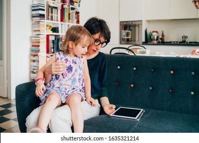 mother and daughter indoor using tablet sitting couch – learning, entertainment, teaching concept
