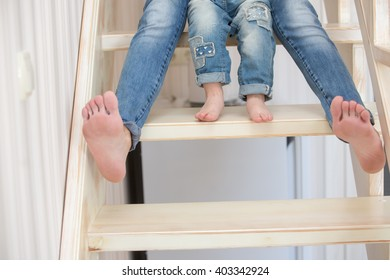 Mother and daughter indoors sitting on the stairs