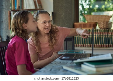 Mother and daughter infront of the laptop studying online