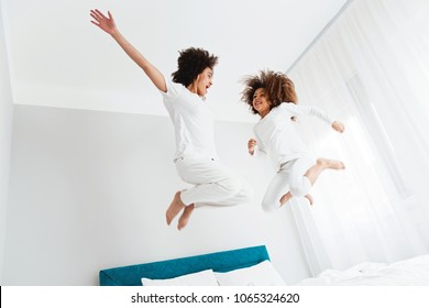 Mother and daughter jumping on the bed, happiness, joyful