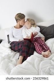 Mother and daughter kissing in bed while reading a book