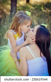 Mother and daughter kissing  in the park