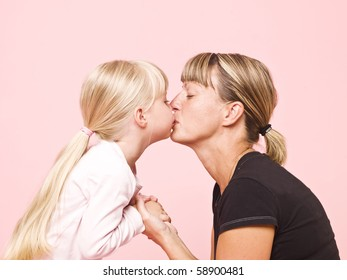 Mother and daughter kissing towards pink background